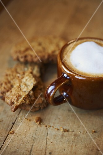 Latte with Foam; Oatmeal Raisin Cookies; On Wooden Surface