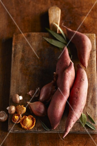 Sweet Potatoes, Mushrooms, Shallots, Sage and Bay Leaves on a Cutting Board; From Above