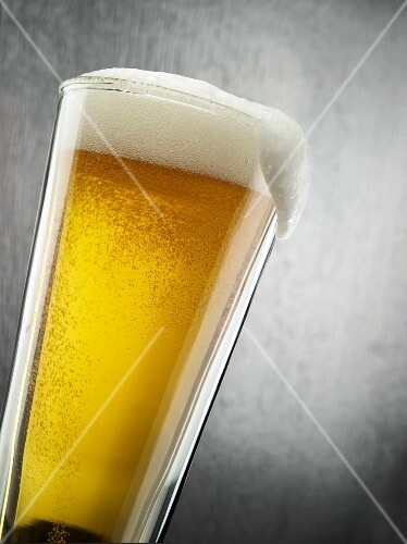 Glass of Light Beer with Foam Spilling Over