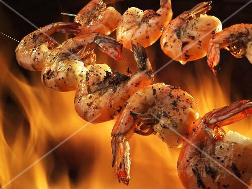 Two Skewers of Seasoned Shrimp Over an Open Flame