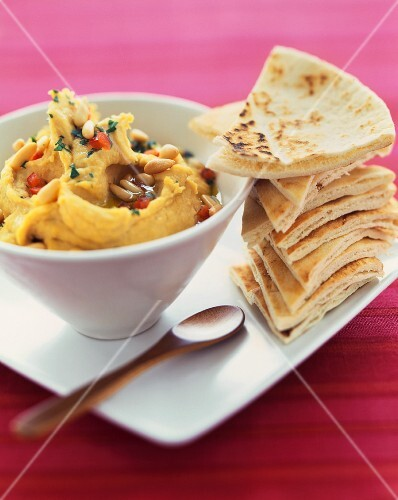 Bowl of Hummus with a Stack of Pita Triangles for Dipping