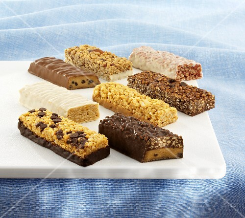 Various Protein Bars on a White Cutting Board