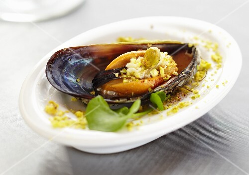Single Mussel with Pistachio Nuts on Small White Dish