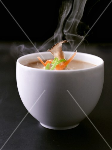 Steaming Bowl of Cream of Mushroom Soup with Mushroom and Carrot Garnish