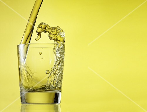 Scotch Pouring into a Glass on Yellow Background