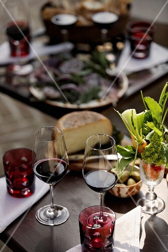 Red wine glasses and starters on a decorated table