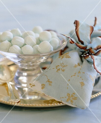 Sweets served in a glass bowl are presented alongside handmade bags intended as gifts for guests