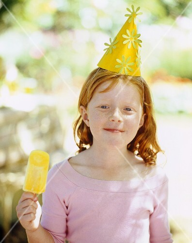 A young girl at a summer birthday party enjoying an ice lolly