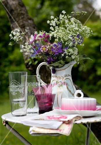 Glasses and butter dish in front of a pitcher filled with garden flowers