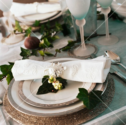 Close-up of cream linen napkin on pewter-edged plates on Christmas table decorated with ivy leaves
