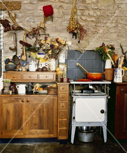 Old-fashioned oven in country kitchen with wooden cupboards and stone walls