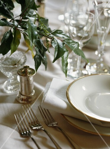 Close-up of silver pepperpot and white plates and napkins onwhite tablecloth