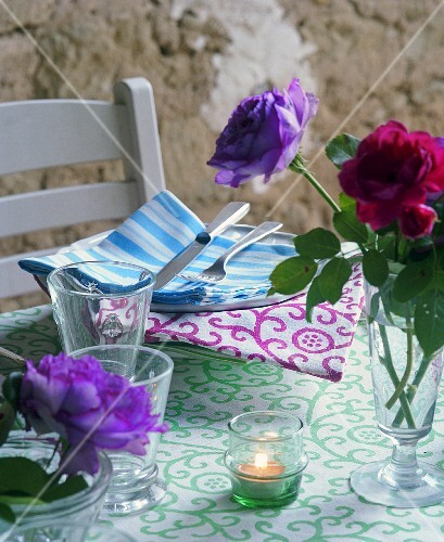 Fresh roses from the garden provide simple centrepieces and add extra colour to the table with patterned tablecloth and napkins