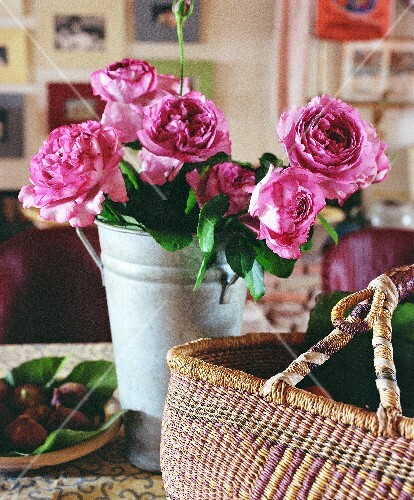 A still-life of a jug of roses and a basket on the kitchen table