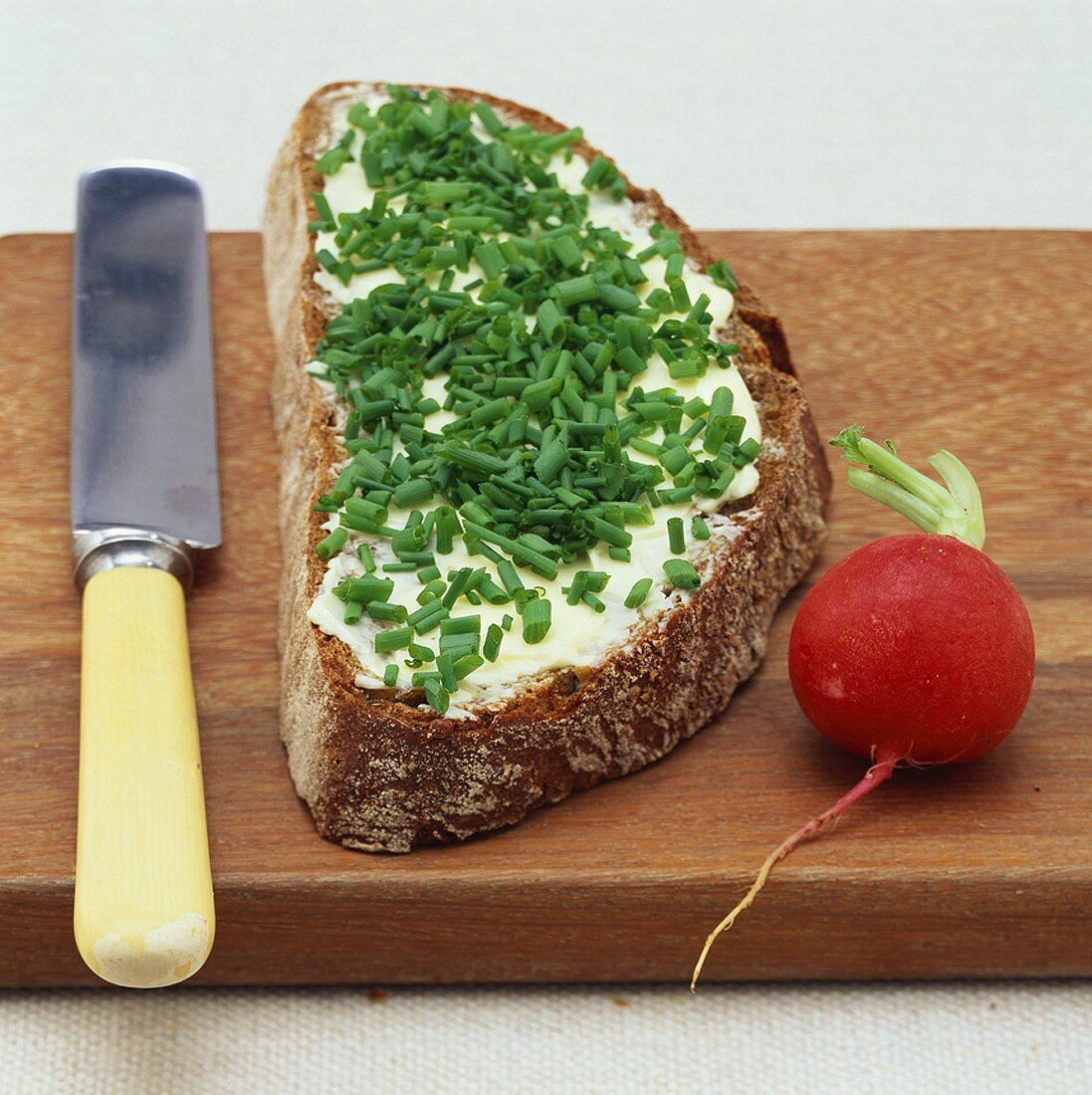 A slice of bread and butter with chives