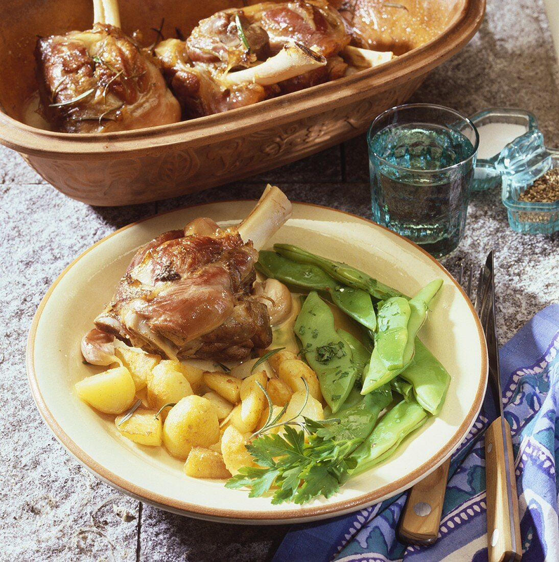 Lamb shanks cooked in Römertopf with potatoes and beans