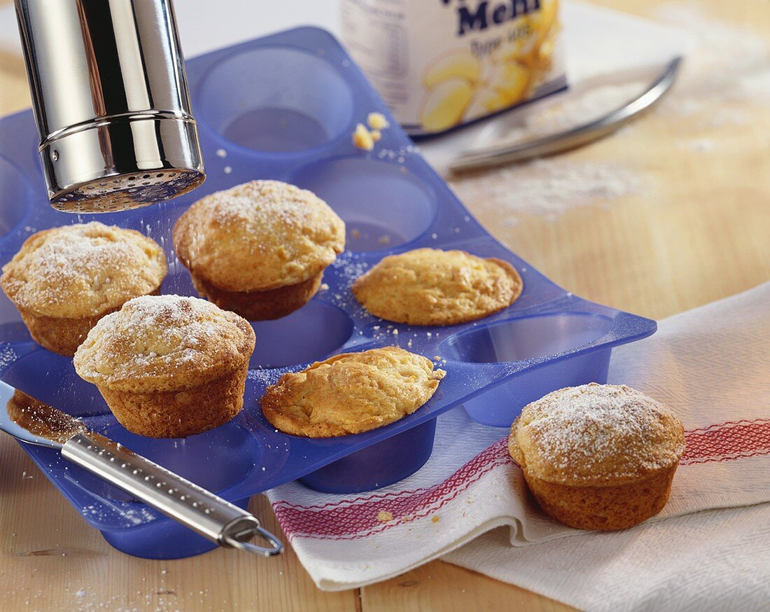 Dusting muffins with icing sugar