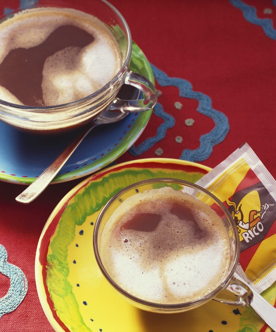 Two cafe con leche (milky coffees) in glass cups