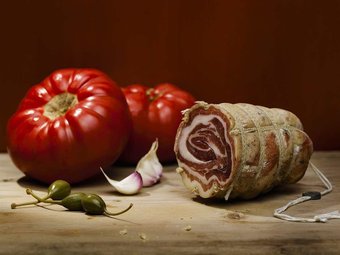 Italian still life: tomatoes, capers, garlic and coppa