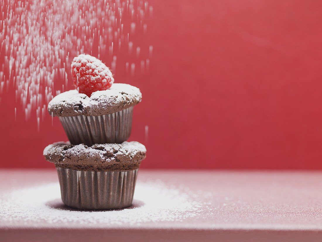 Two chocolate muffins being sprinkled with icing sugar