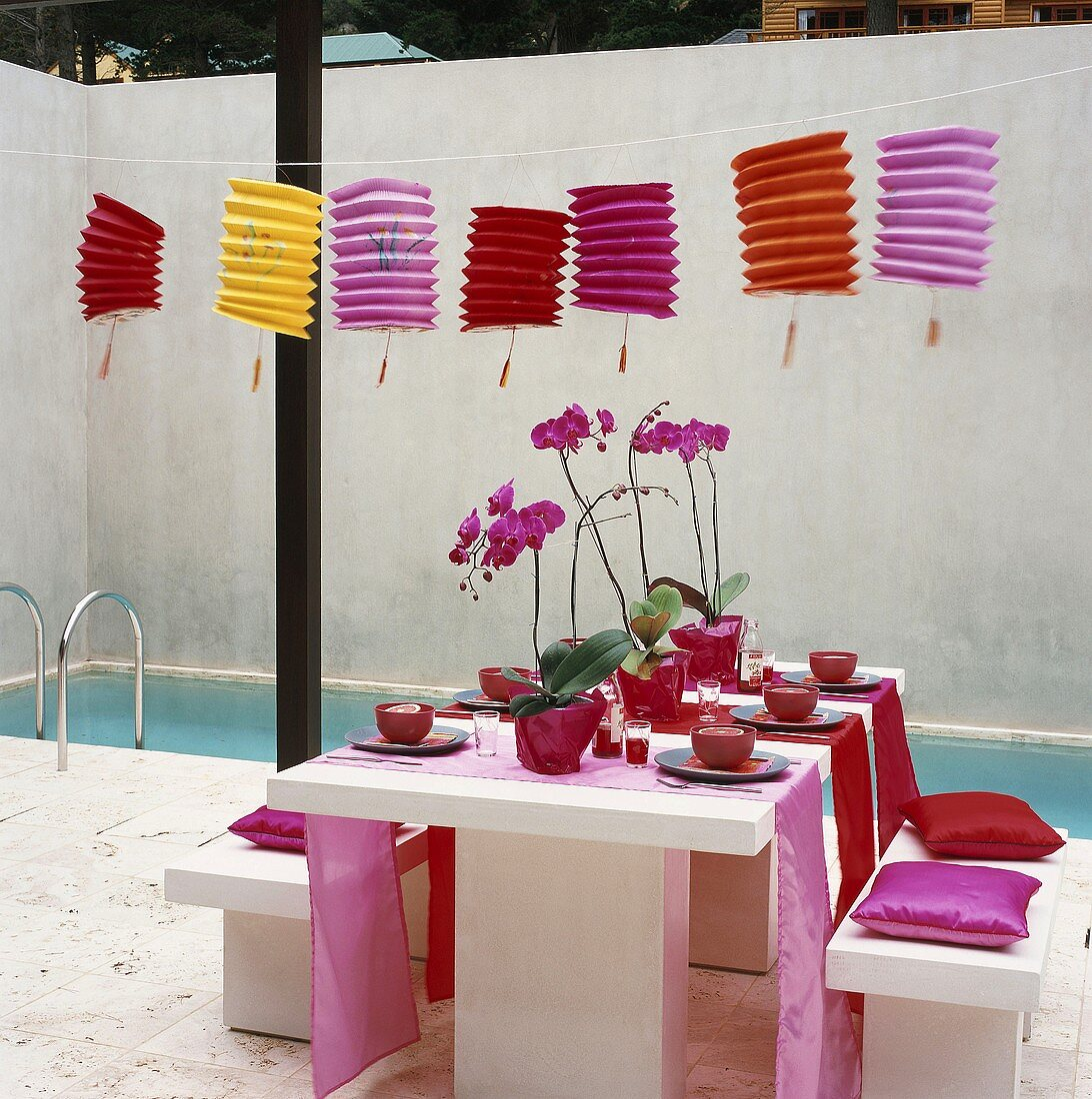 Cheerful courtyard with pool, lanterns and festively set table