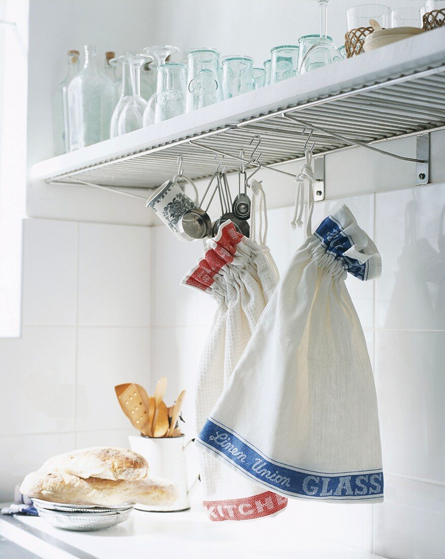 Tea towels hanging from kitchen shelf
