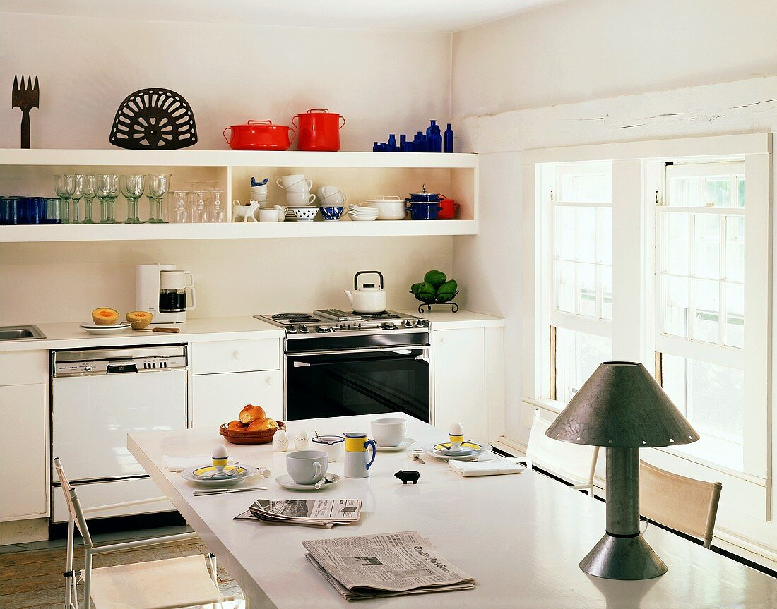 Simple, cheerful kitchen with crockery on long shelves and table lamp on white table