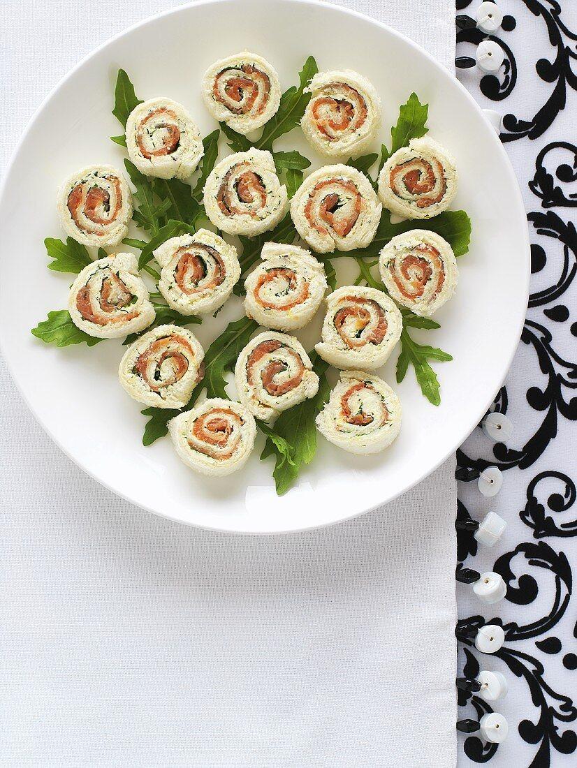 Several salmon pinwheel sandwiches on a plate