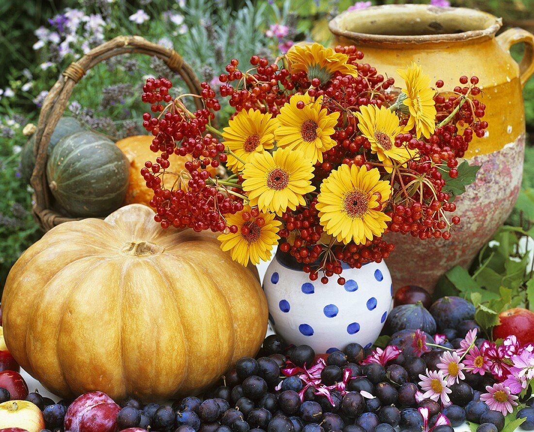 Autumnal still life with vase of flowers, pumpkins & fruit