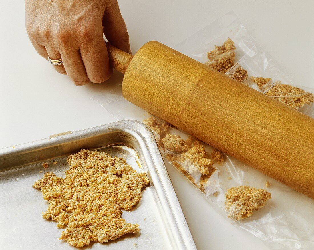 Crushing sesame brittle in plastic bag with rolling pin