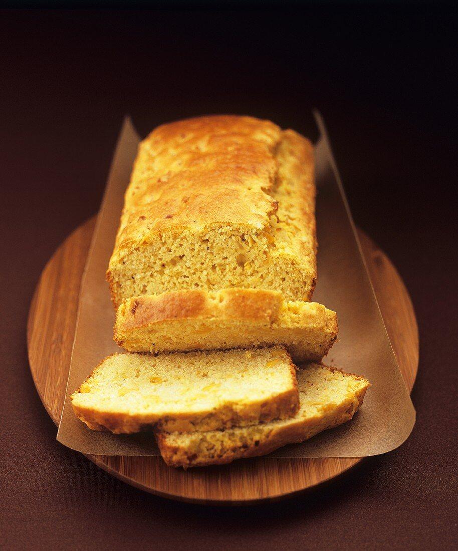 Cornbread, partly sliced, on wooden board