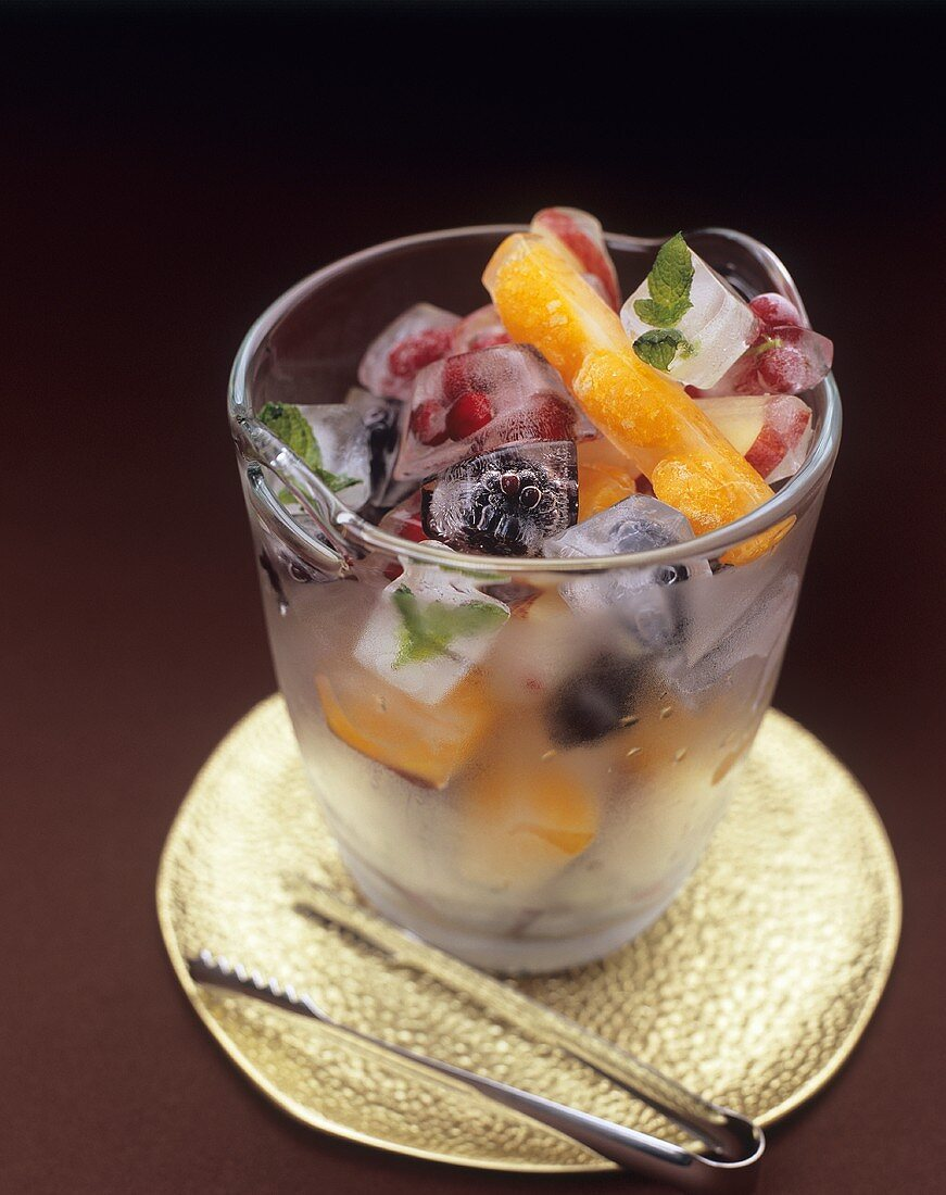 Ice cubes containing frozen fruit and mint