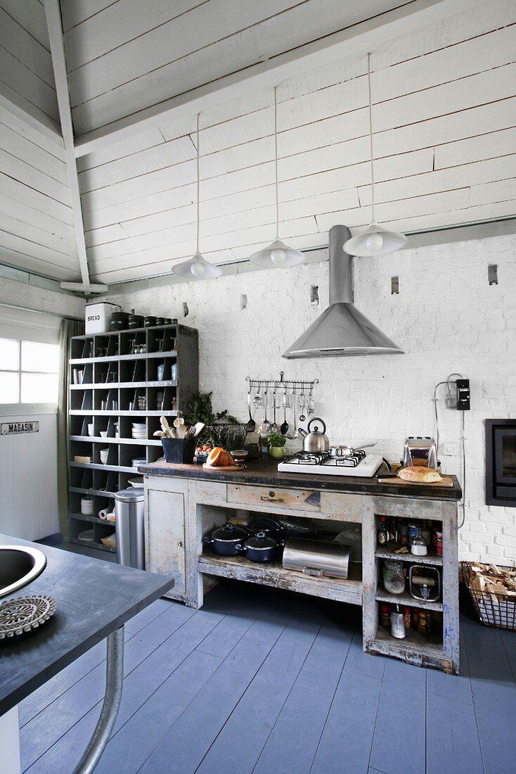Ein antiker Küchentisch mit integrierter Gasherdplatte und vielen Küchenutensilien