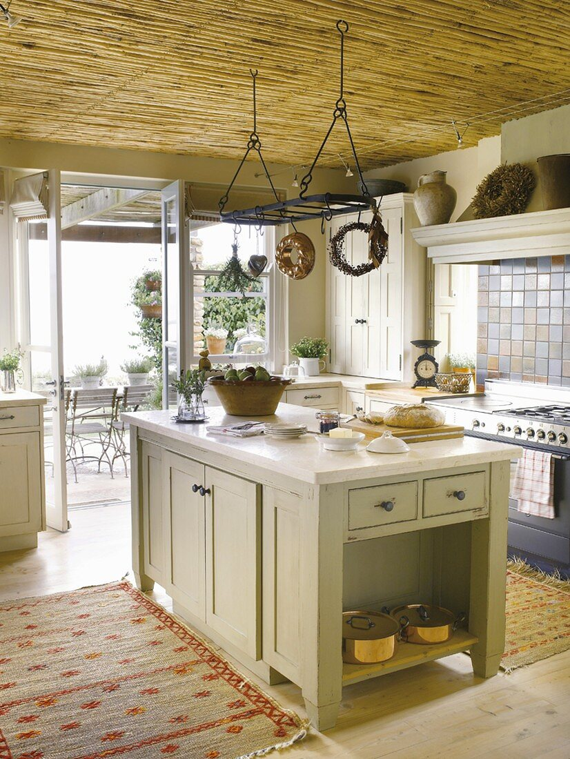 Küchenblock in einer gemütlichen Landhausküche mit Terrassenzugang und abgehängter Bambusdecke