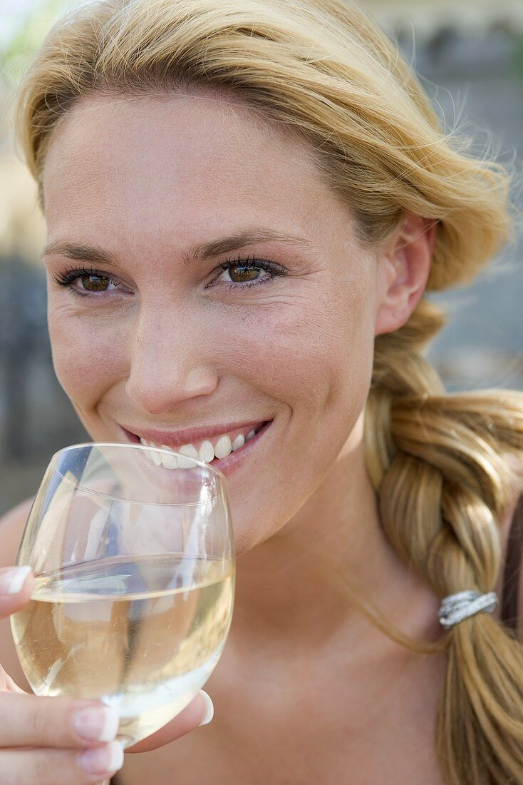 Blond woman drinking a glass of white wine
