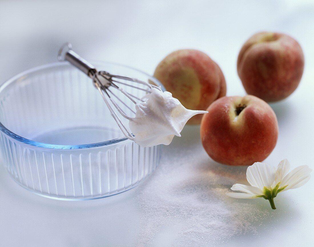 Still life with peaches, beaten egg white, whisk, sugar