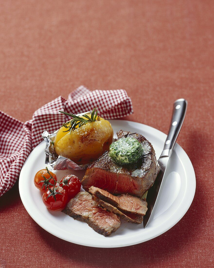 Beef steak with herb butter, tomatoes and baked potato