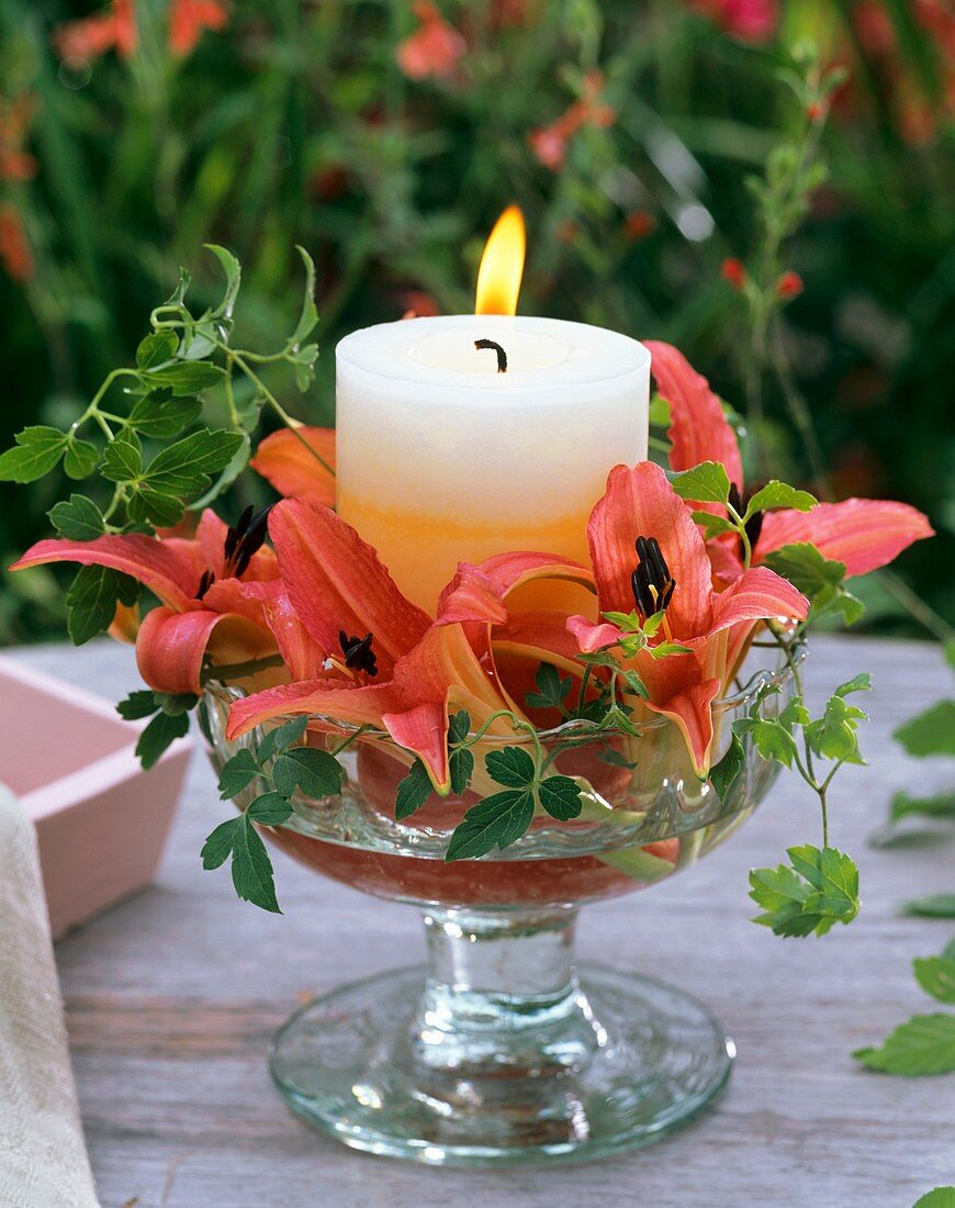 Candle, day lilies and clematis in glass