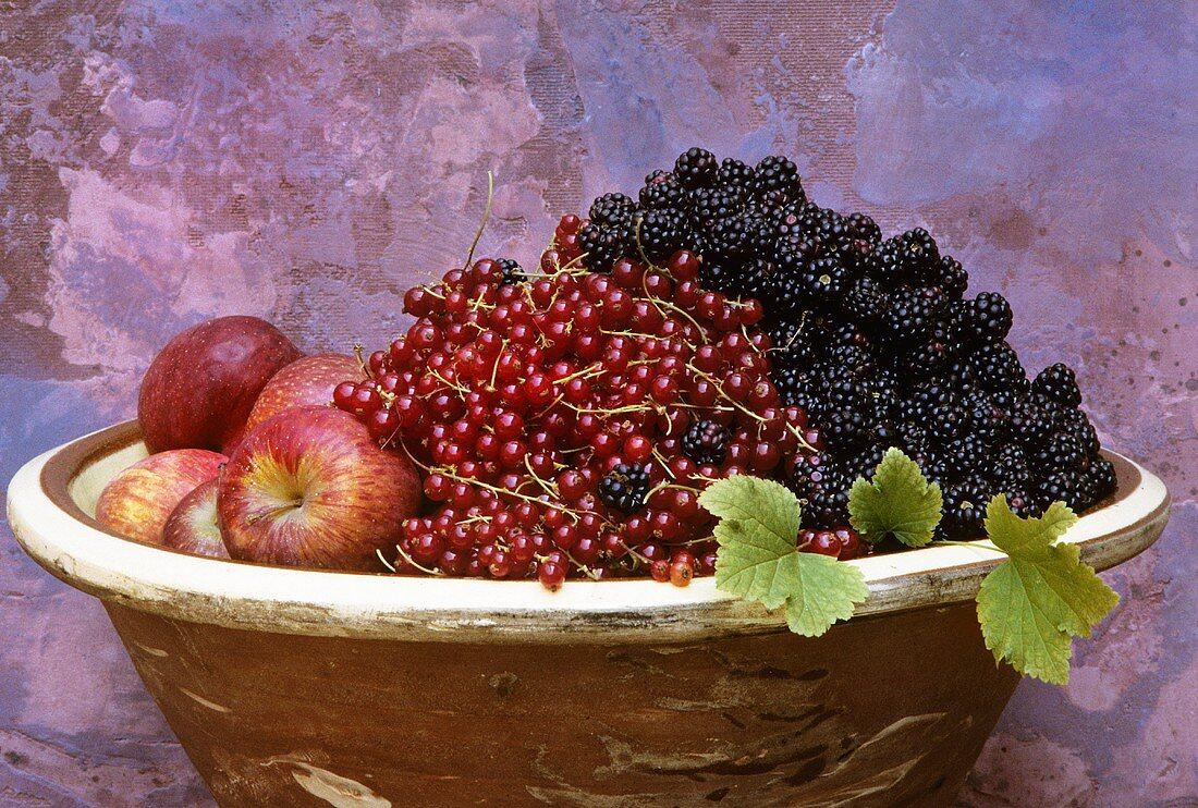 Apples, blackberries and redcurrants in terracotta bowl