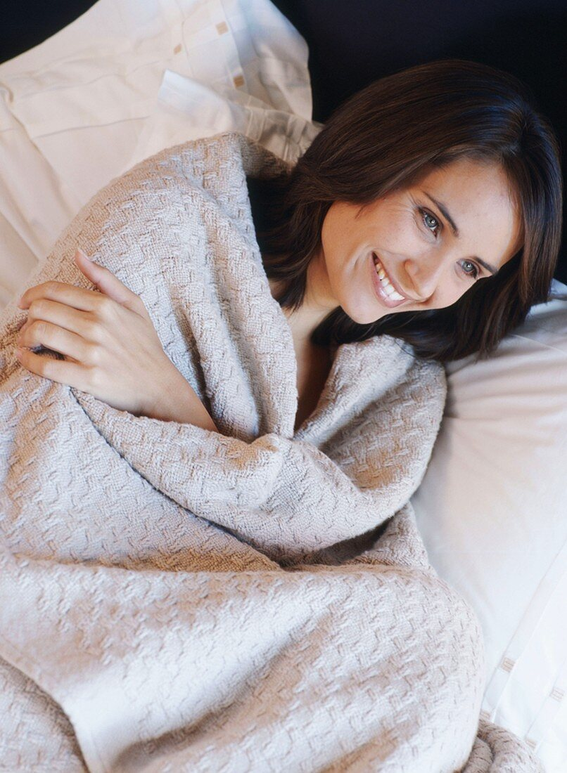 A woman lying wrapped in a woollen blanket