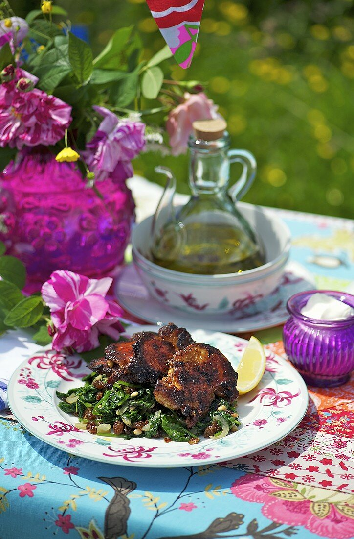 Crispy chicken with char and raisins on a garden table