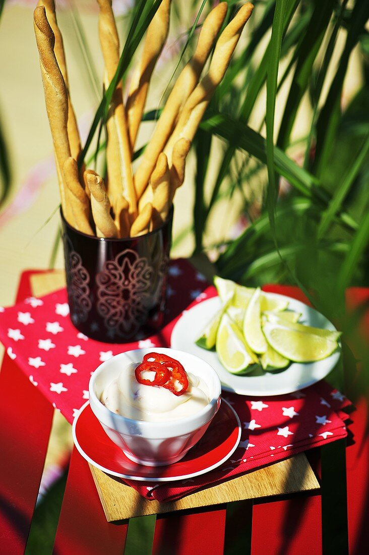 Chilli mayonnaise, slices of lime and grissini