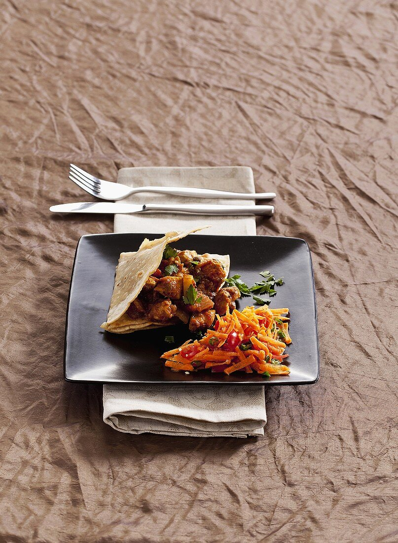 Chicken curry in roti with carrot salad