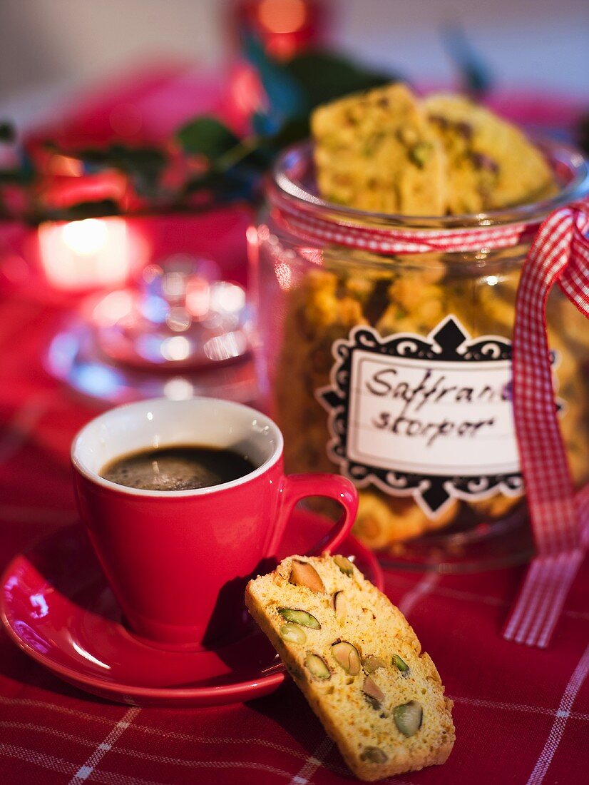 Pistachio and saffron biscuits in a cookie jar with a cup of espresso