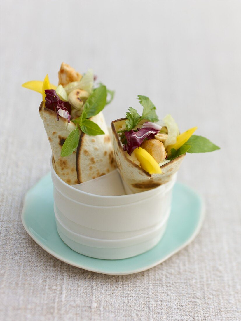 Two chicken and mango wraps in a china dish
