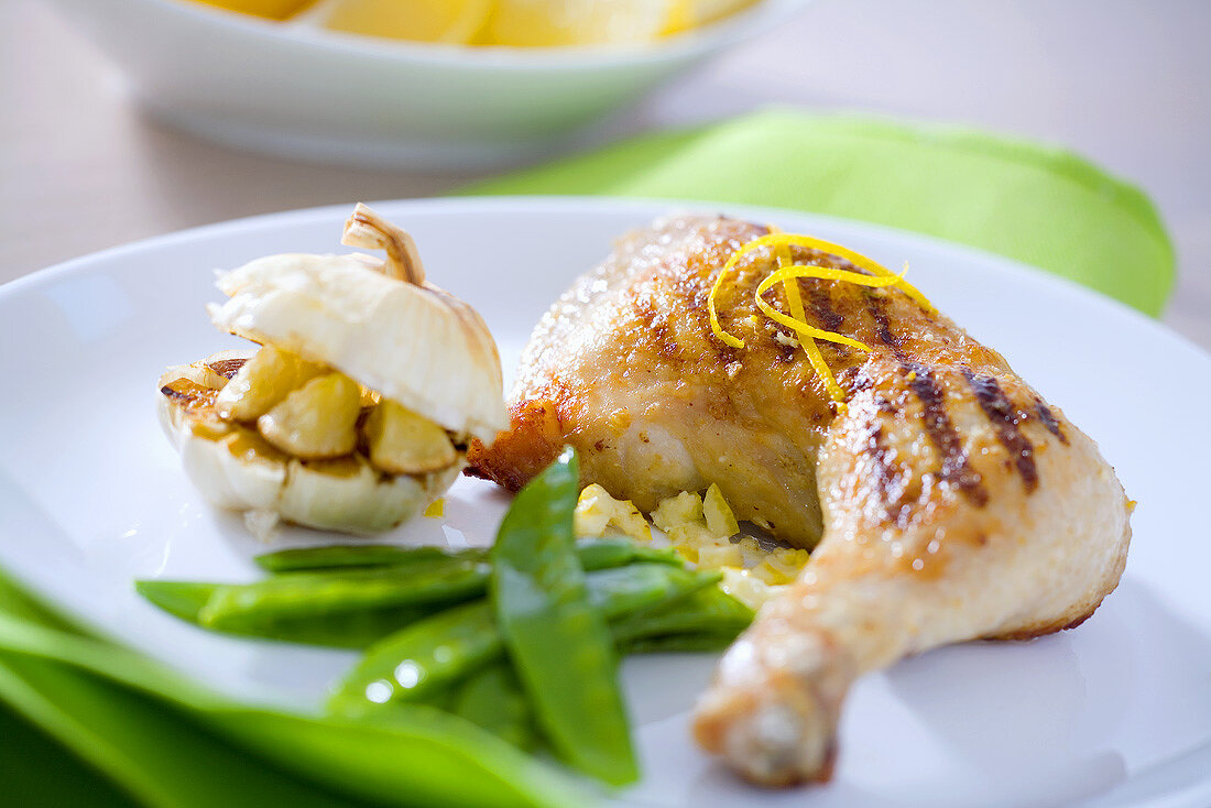 Grilled chicken leg with garlic and mangetout