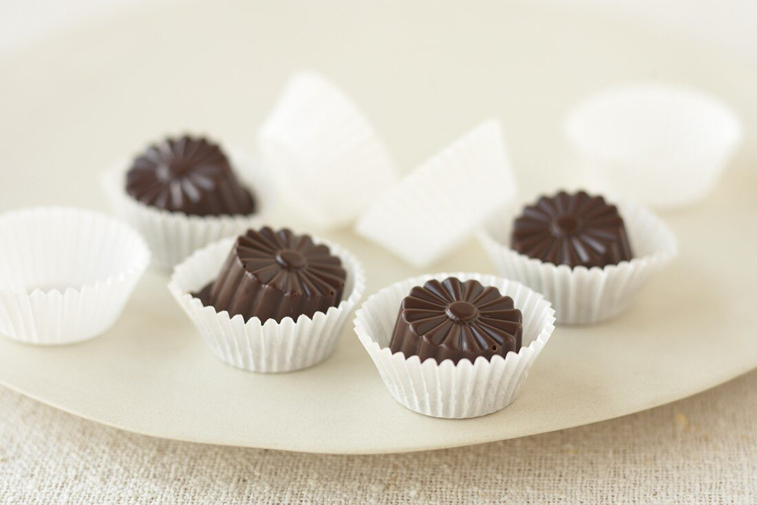 Four coconut chocolate truffles in paper cases