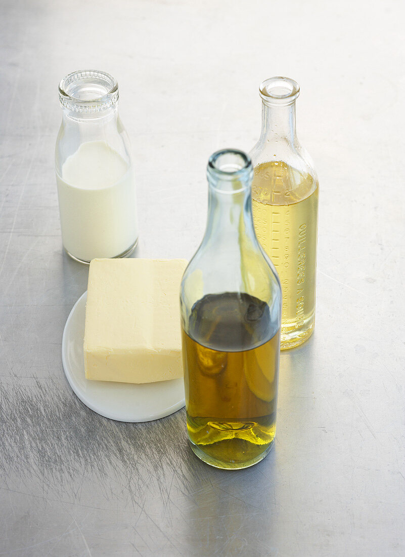 Olive oil, rapeseed oil & milk in glass bottles with butter