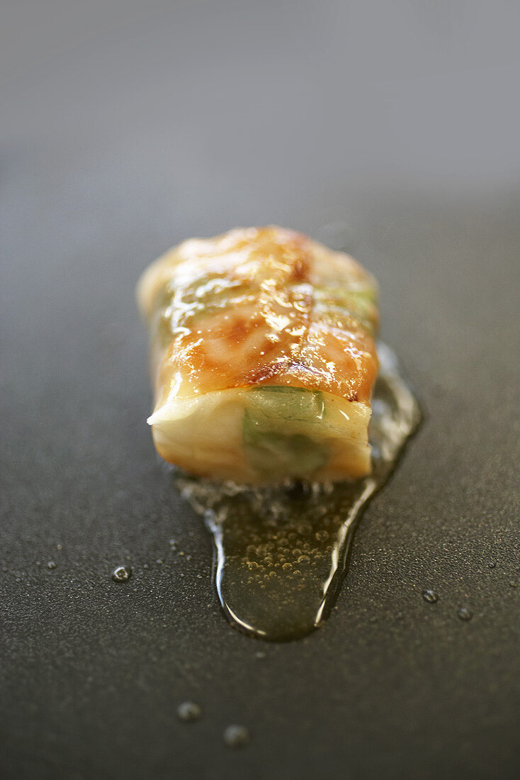 Frying a piece of halibut wrapped in mint and ham