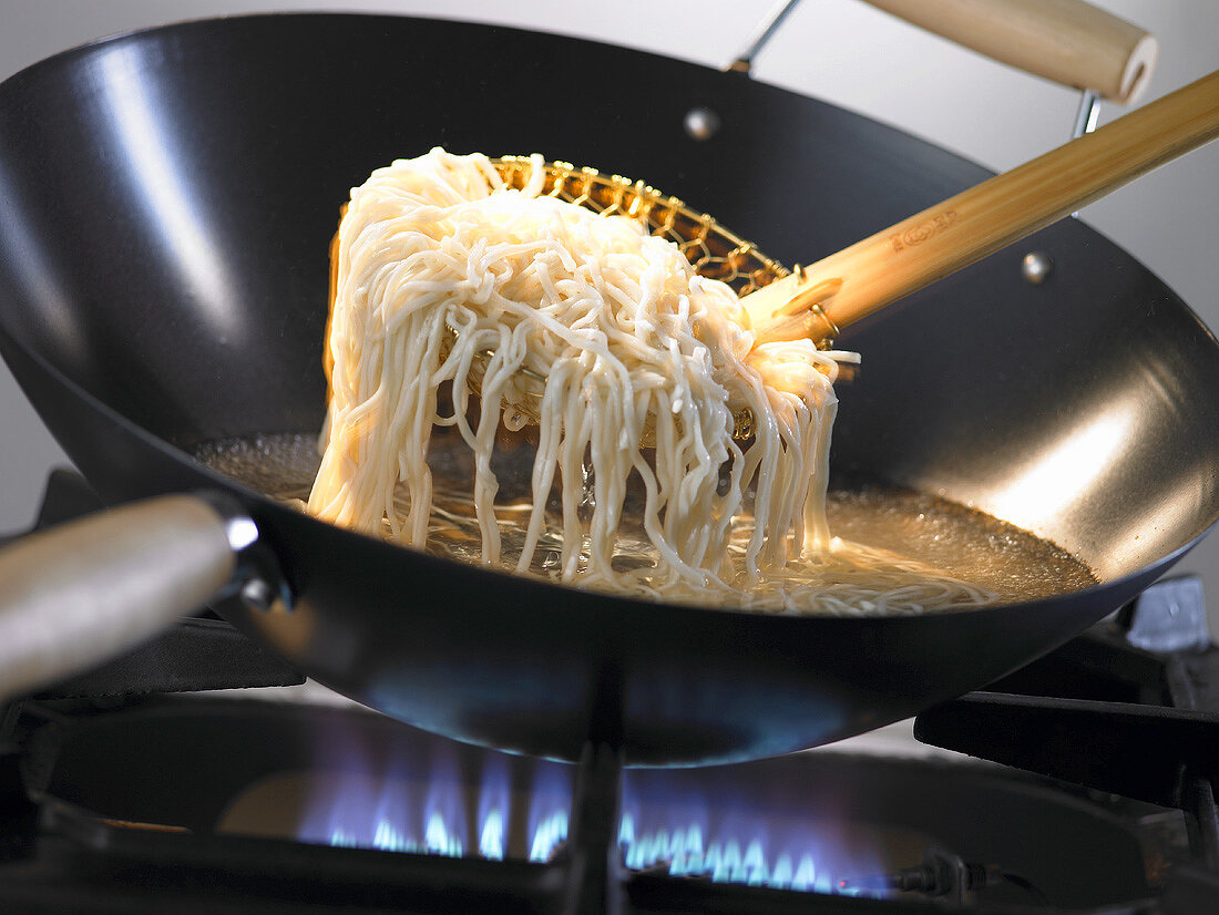Rice noodles being placed in a wok with a skimmer